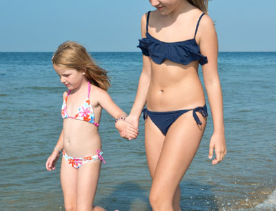 two young girls walking on the beach